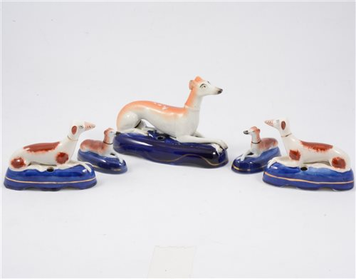 Lot 10-Two pairs of Staffordshire miniature reclining dog pen stands, and a larger fifth stand (5)