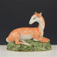 Lot 14-Staffordshire lead glazed earthenware figure of a recumbent deer, 14cm.