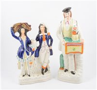 Lot 89-Staffordshire figure, Organ Grinder, and a theatrical group (2)