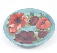 "Lot 7-A Moorcroft ""Anemone"" shallow dish on smokey blue/green ground, 25.5cm, signed and impressed Moorcroft Made in England."