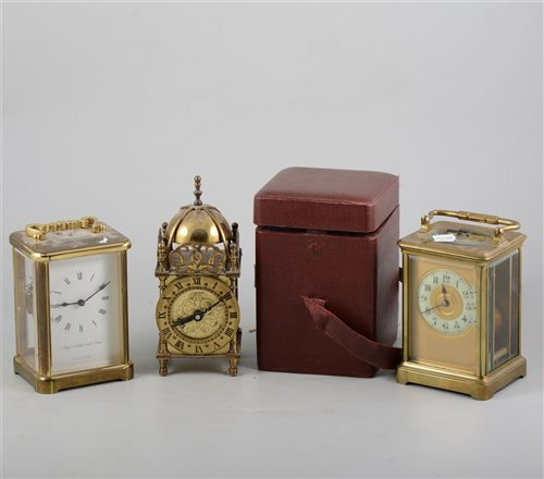 Lot 152-Brass carriage clock, enamelled dial, 15cm, leather travelling case, another brass cased carriage clock and a miniature lantern clock with battery movement, (3).