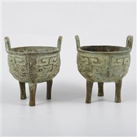Lot 75-Pair of archaic style Chinese patinated bronze tripod censers