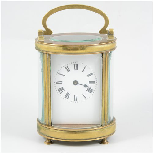 Lot 83-An oval brass cased carriage clock, with bevel glass panels.