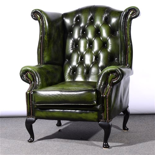 Lot 491 - Traditional style close studded green leather wing-back easy chair, on cabriole legs, width 93cm.