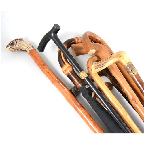 Lot 95-A collection of walking sticks and an umbrella.