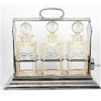 Lot 158-Walker & Hall silver plated three-bottle tantalus, with key.
