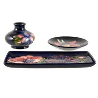 Lot 532-Three items of Moorcroft Pottery, including an 'Orchid' design coaster, 'Anemone' tray, and another vase..