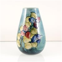 Lot 530-A Moorcroft Pottery vase, designed by Walter Moorcroft, exotic flowers on a smokey blue ground.