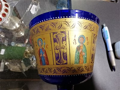 Lot 23-A Bohemian ruby glass pedestal dish overlaid in white and gilt with eight floral vignettes, and a Bristol blue goblet with heavily gilded ecclesiastical panels depicting saints