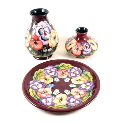 "Lot 40-A Moorcroft Pottery plate, ""Pansy"" designed by Rachel Bishop, 1994, 25.8cm diameter, and two vases of the same design and date, 11cm and 19cm."