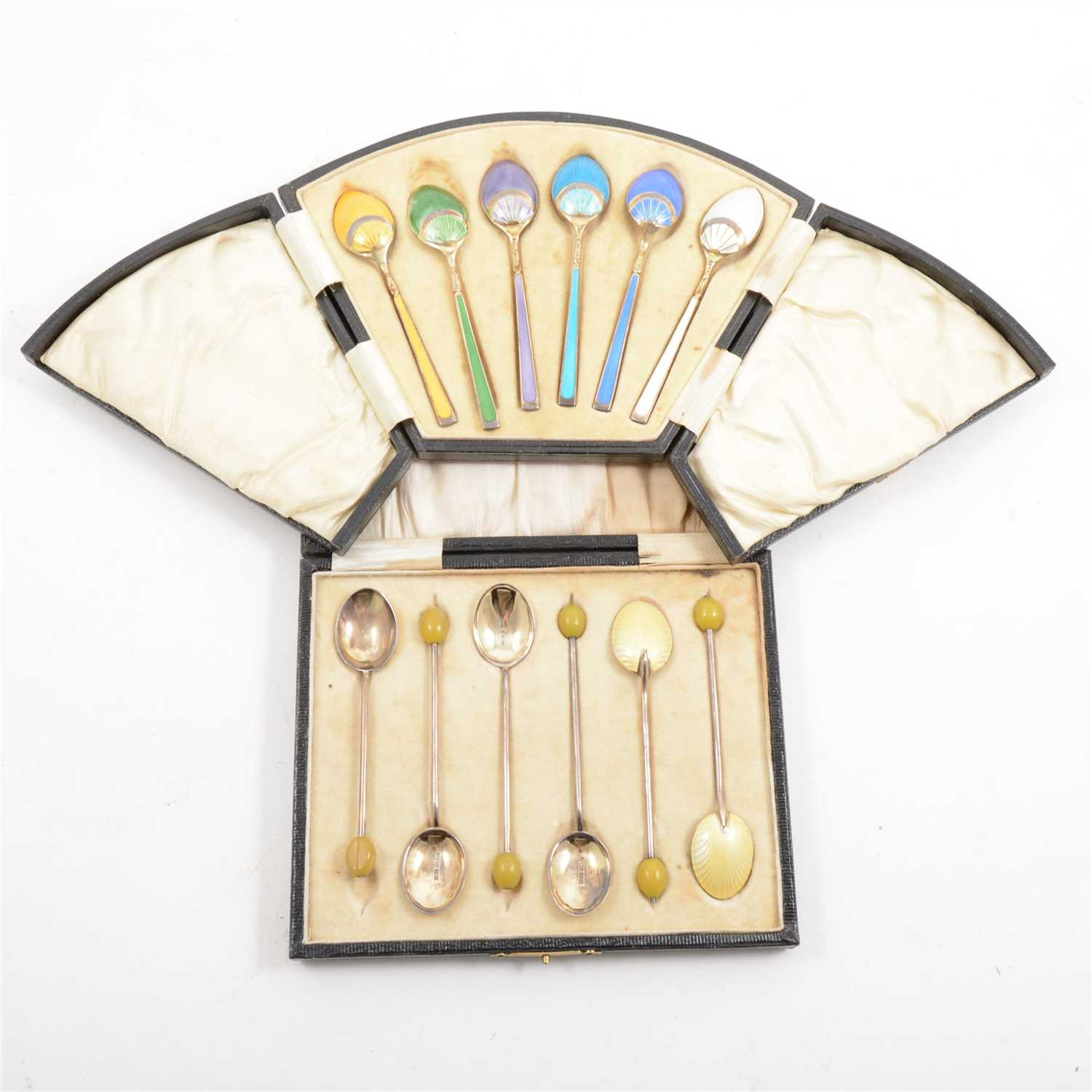 Lot 244 - A cased set of silver gilt and enamelled teaspoons by Levi & Salaman, Birmingham 1925, and a cased set of silver and enamelled coffee spoons by Henry Clifford Davis, bean finials, Birmingham 1926.