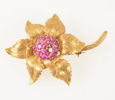 Lot 71-An 18 carat yellow gold and ruby floral brooch.