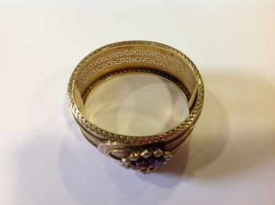 Lot 94-A late 19th Century yellow metal bangle with an amethyst, diamond and pearl cluster.