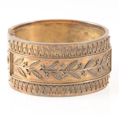 Lot 95-A mid 19th Century yellow metal 33mm wide half hinged bangle