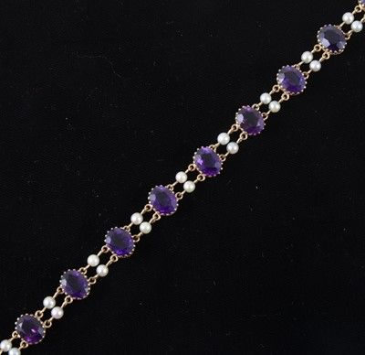 Lot 91-An amethyst and pearl bracelet, strung with ten oval cut stones