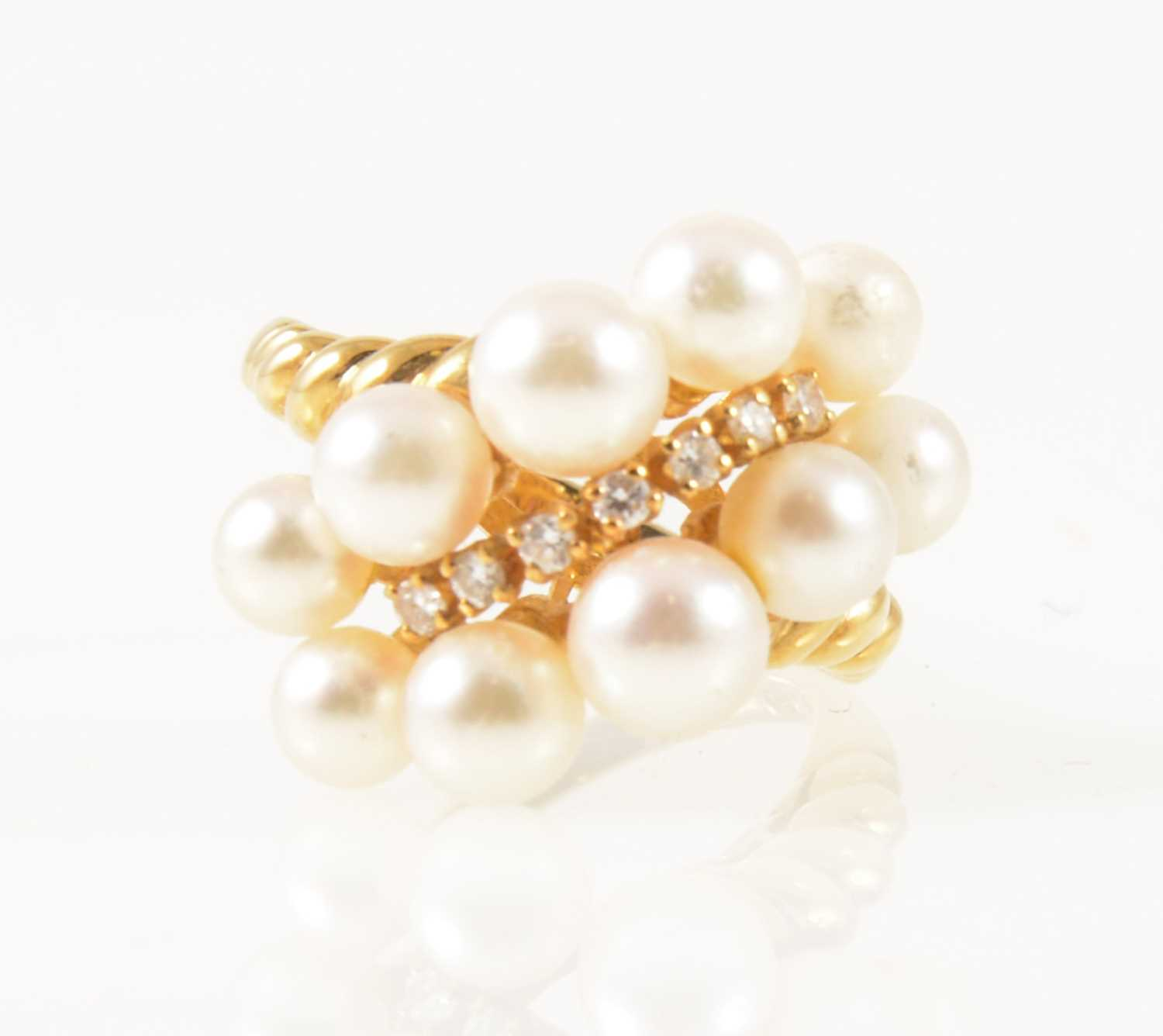 Lot 35-Mikimoto -  an 18 carat yellow gold dress ring set with seven graduated small diamond and pearls.