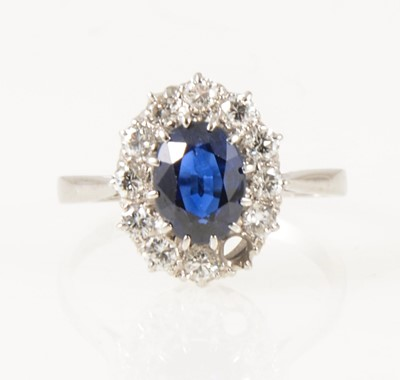 Lot 23-A sapphire and diamond oval cluster ring.