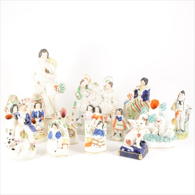 Lot 39-A collection of thirteen Staffordshire figures, spill vases, and pen stands