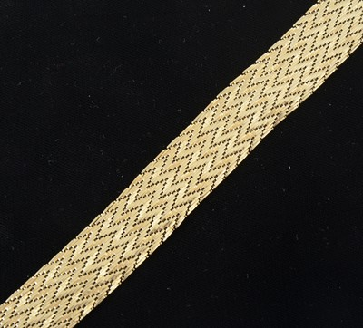 Lot 86-An 18 carat yellow gold 20mm wide flexible herringbone design bracelet.