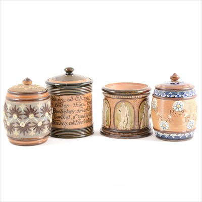 Lot 9-Four Doulton Lambeth tobacco jars, including a John Broad Cricketers jar