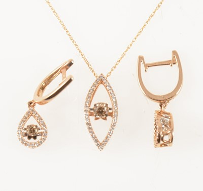 Lot 51-A dancing diamond pendant and pair of matching earrings.