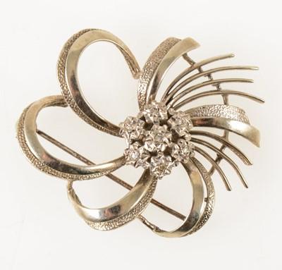 Lot 62-A white metal diamond set swirl brooch.