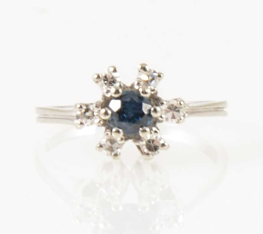 Lot 22-A sapphire and diamond circular cluster ring.