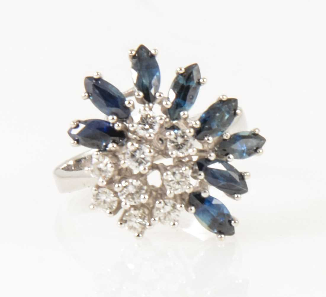 Lot 24-A modern sapphire and diamond cluster ring.