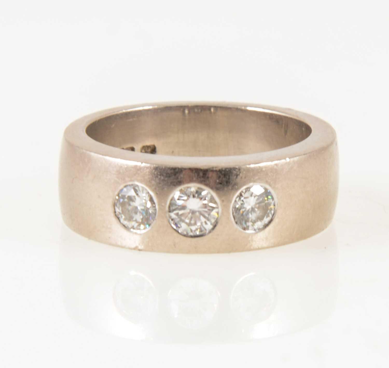 Lot 11-A lady's/gentleman's diamond three stone ring.