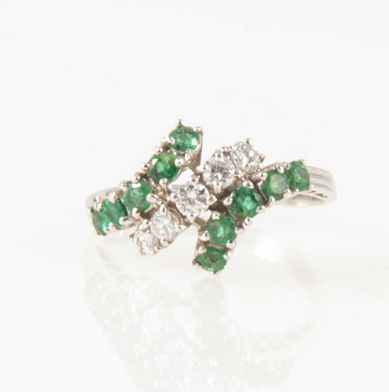 Lot 30-An emerald and diamond crossover ring.