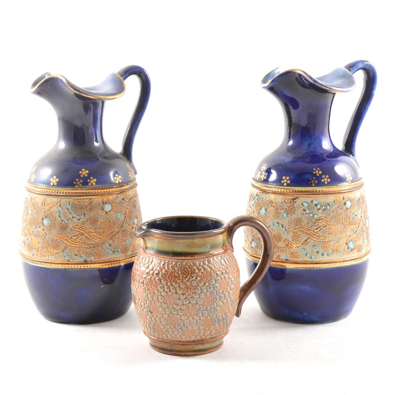 Lot 5-A pair of blue ground Doulton & Slaters stoneware ewers, and another cream jug.