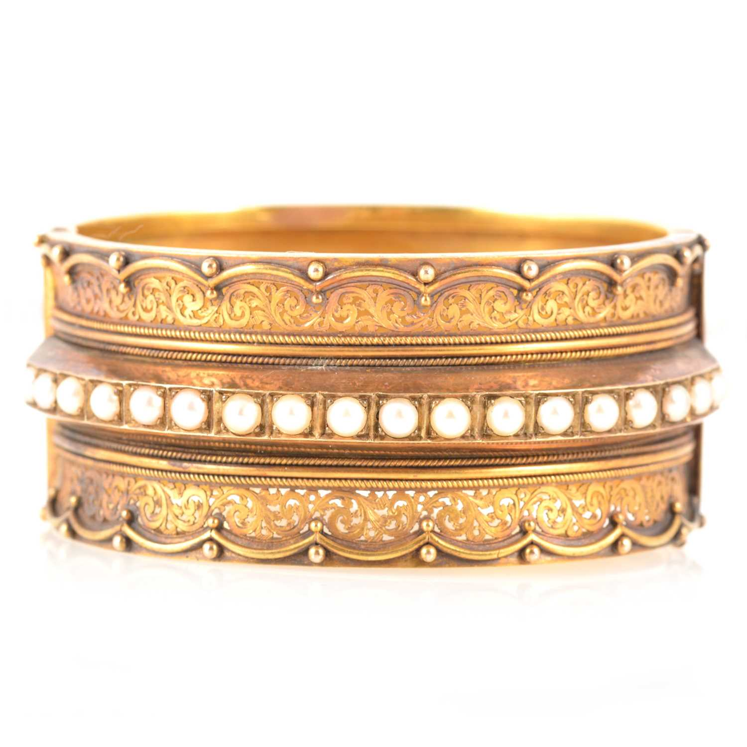 Lot 212 - A Victorian yellow metal half hinged bangle set with pearls.