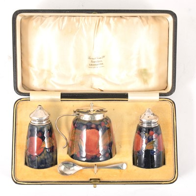 Lot 15-A three-piece silver-mounted William Moorcroft 'Pomegranate' pattern cruet