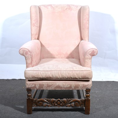 Lot 34 - A wing-back easy chair.