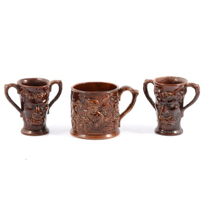 Lot 27 - Staffordshire treacle-glazed frog mug and pair of Bacchus mask Loving Cups.