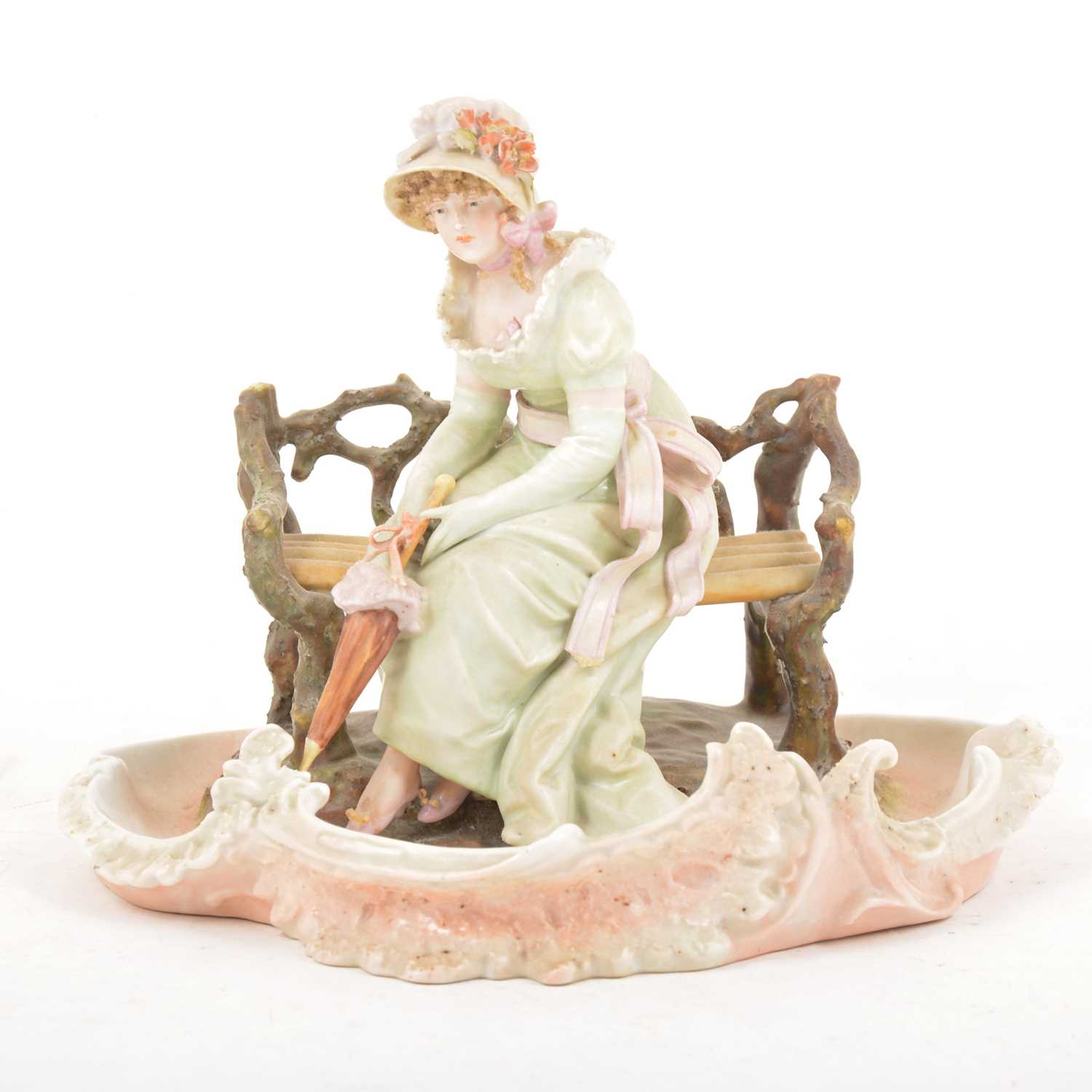 Lot 17 - A Continental porcelain centrepiece of a lady seated on a bench