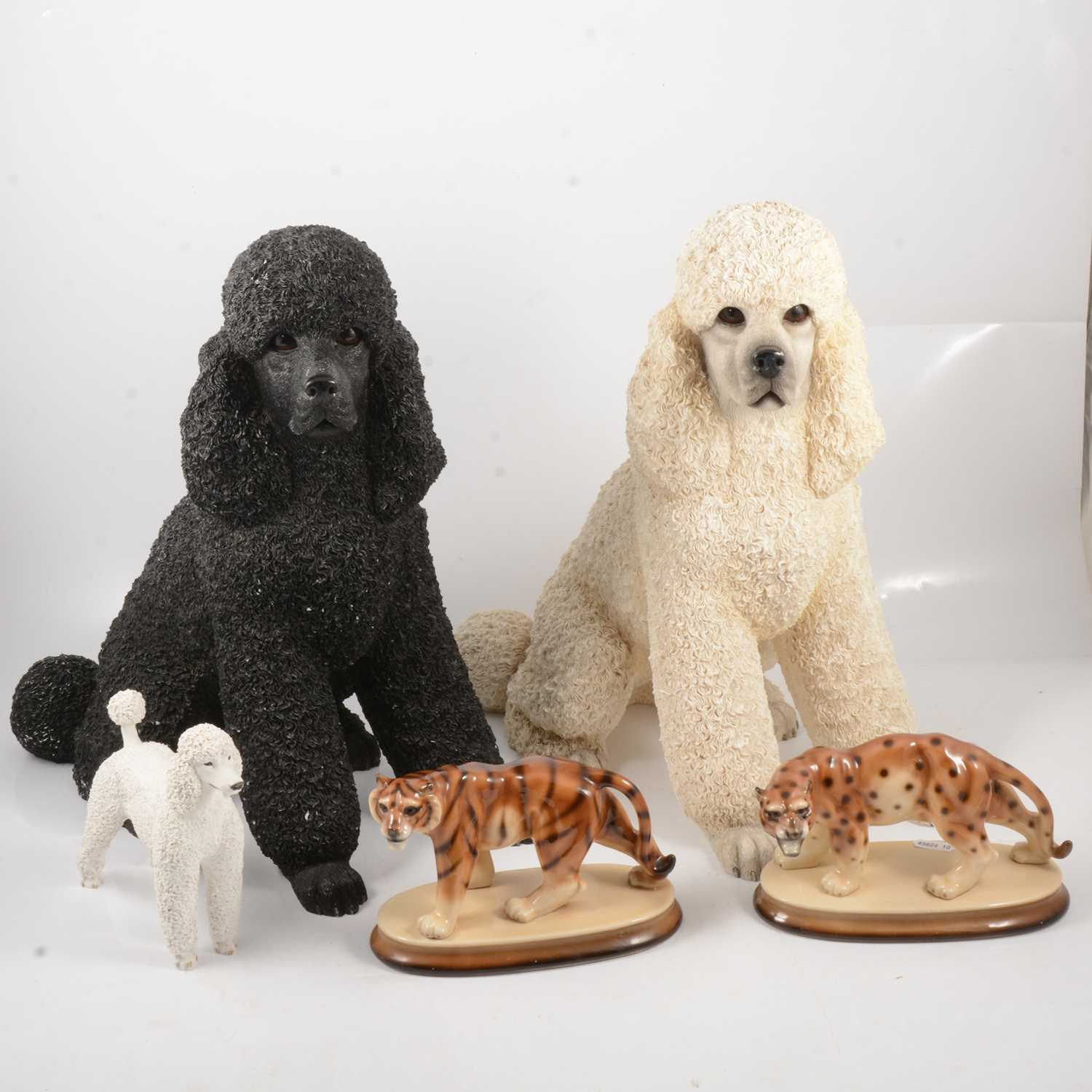 Lot 34 - Two large resin poodles, other poodle models and ornaments